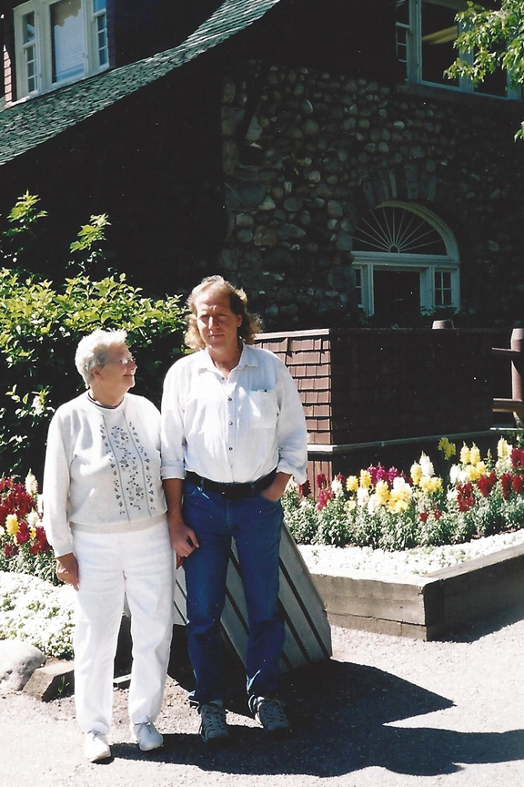 Man standing with his mother while his mother smiles at him in front of yellow, red, and white flowers.