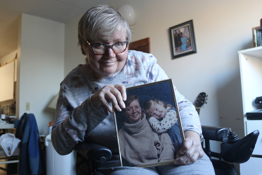 Woman smiling in wheelchair while she holds photo of her and her daughter in her apartment.