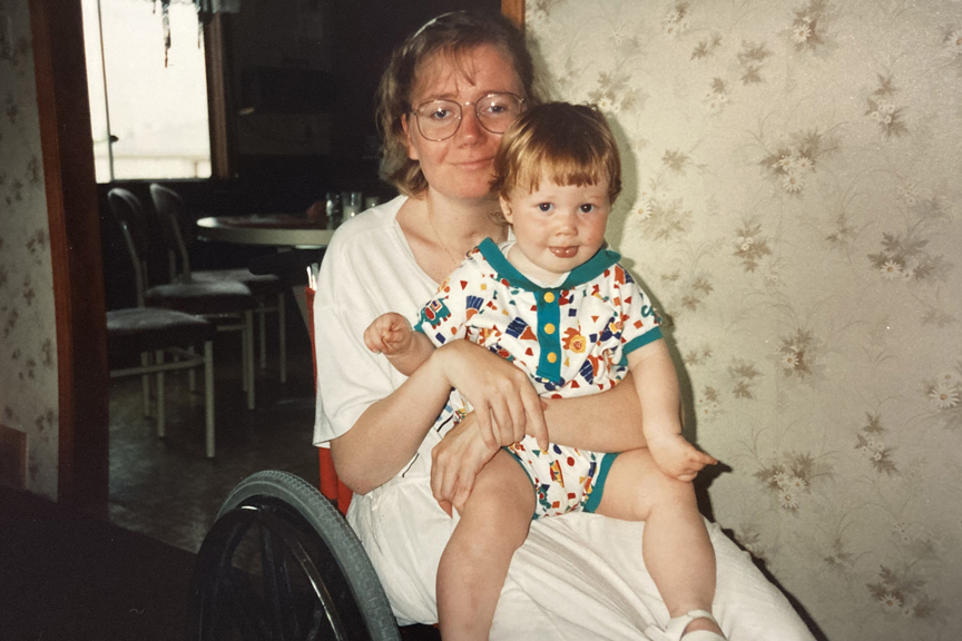 Women sits in her wheelchair while holding her orange haired child.
