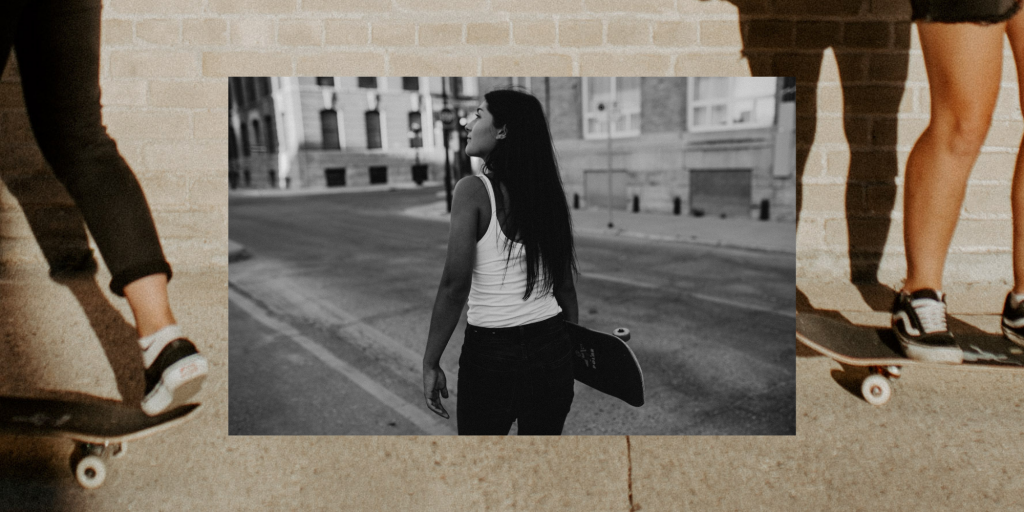 Black and white photo of girl with skateboard, walking downtown. Layered behind is another skateboard photo of two girls' feet on their skateboards.
