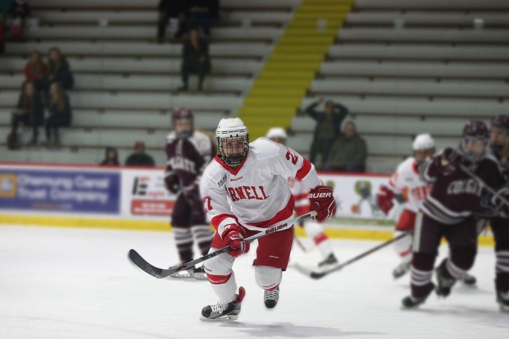 Female hockey player skates in a hockey game.