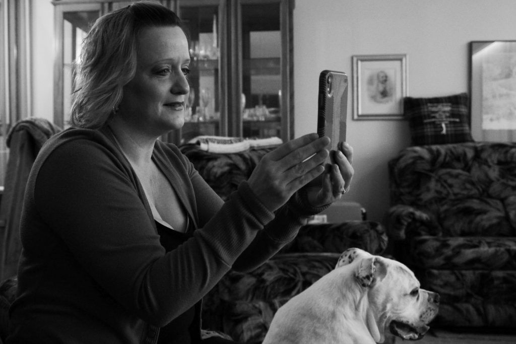 A woman in her 40s smiles as she holds her smartphone in front of her. She's in her living room, surrounded by plush couches, a China cabinet, and a large bulldog.