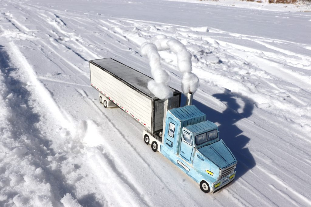 Overhead view of a model transport truck navigating an ice road.